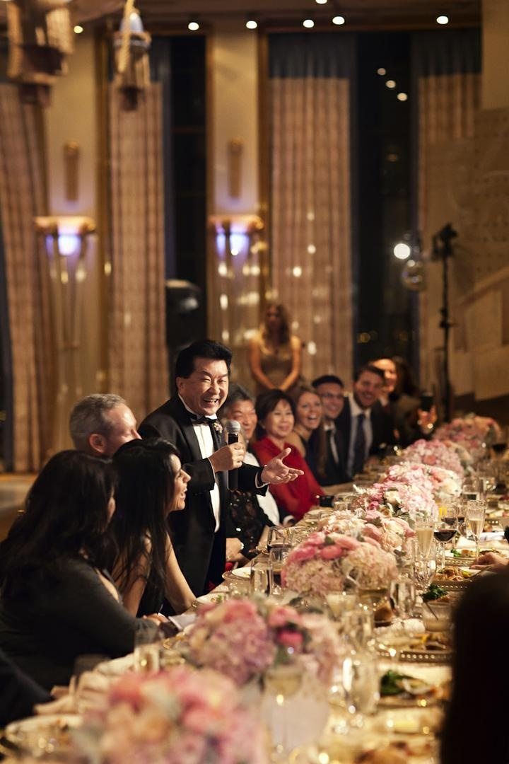 Wedding guest giving speech with microphone at table