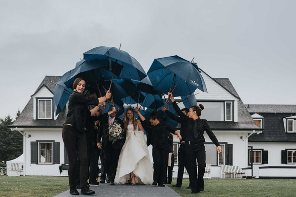 wedding ceremony in the rain bride and father walking to tent with staff holding umbrellas