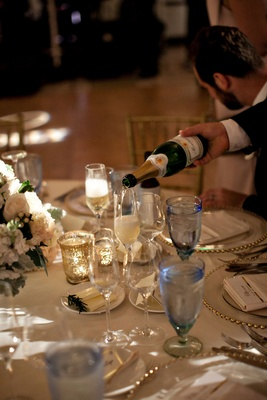 Wedding reception server pouring champagne sparkling wine into glass of wedding guest