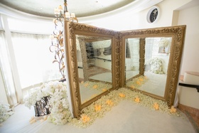 two large mirrors with gold frames with seating chart, ivory petal at the base