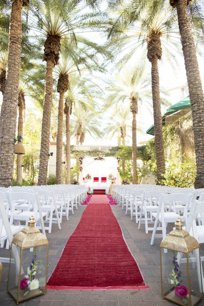 south asian wedding inspiration, palm trees, red carpet aisle runner, lanterns framing aisle