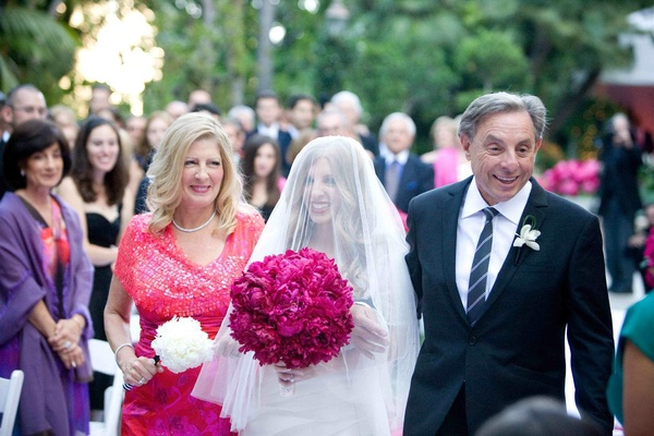 Bride with veil over face walking down aisle with parents