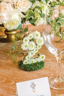 wedding reception table number formed with small flowers, table number made from mums on moss bed