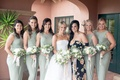 Bride in strapless wedding dress with maid of honor in pattern flower dress and bridesmaids in green
