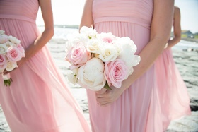 Pink bridesmaids holding white peonies and pink roses