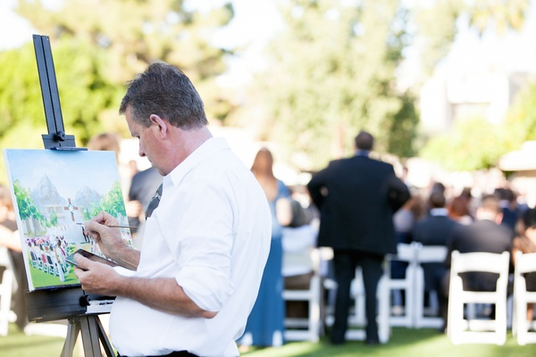 Man in white shirt paints alfresco wedding