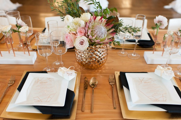 a modern contemporary tablescape white black and copper with green and pink florals and metallics