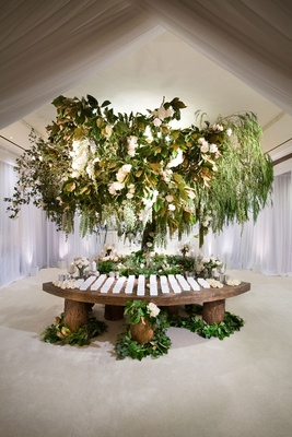 enchanted forest escort card table green leaves white flowers wood tree trunk stumps