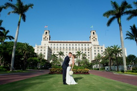wedding reception at the breakers palm beach, bride and groom kiss outside of venue