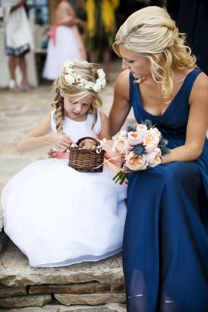 Bridesmaid sitting with young girl in white dress