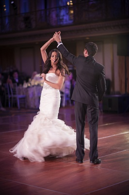 Bride in Vera Wang wedding dress spins during first dance with groom in Chicago