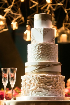 a five-tier white and gold cake each tier in different shapes round or square and designs