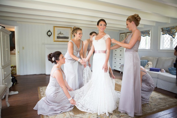 Bride in a Lela Rose lace gown with bridesmaids in long champagne dresses