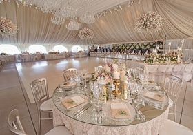 Mirror round table with gold candlesticks and low flower centerpiece around white dance floor