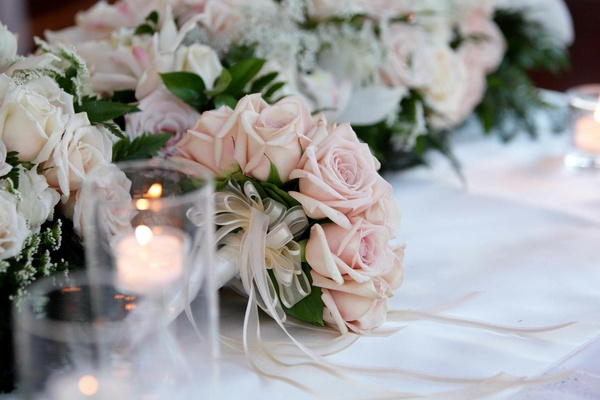 Bouquet of pale pink roses on a wedding reception table