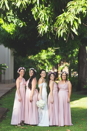 Bridesmaids in pink long bridesmaid dresses with flower crowns instead of bouquets purple orchids
