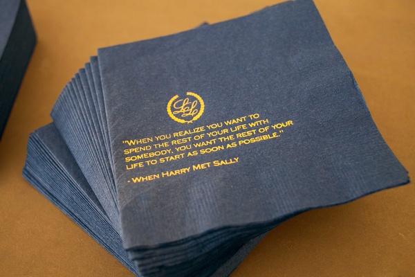 Navy blue cocktail napkin with gold printed monogram and love quote from movie