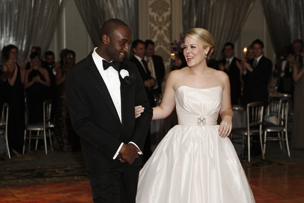 Bride in a strapless Amsale gown with groom in black tuxedo