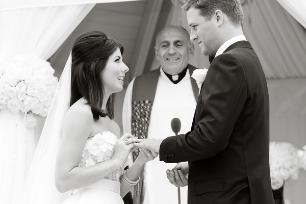 Black and white photo of bride exchanging ring with groom