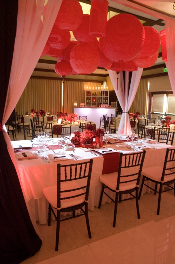 Wedding reception table under red paper lanterns in ballroom