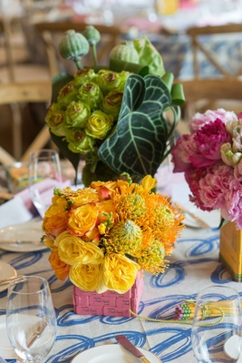 Yellow flowers protea roses in pink eraser vase on table with cursive blue and white linen