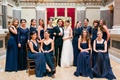 Bridesmaids with couple wearing navy blue bridesmaid dresses
