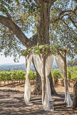 Outdoor wedding ceremony small four post wood arbor with greenery ivory drapery curtains under tree