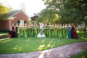 Bride in Isabelle Armstrong wedding dress with 18 bridesmaids in green dresses and red blue dresses