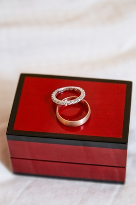 bride and groom wedding bands in on a red ring box diamonds gold