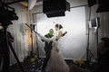 Bride in a strapless Mark Zunino dress with groom dressed in black in slow motion booth
