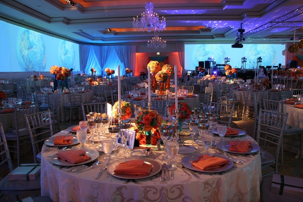 Wedding reception table with candlesticks and orange and blue flowers