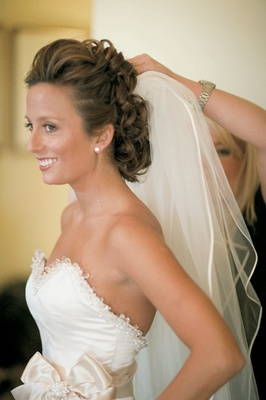 Bride getting ready with curly updo and natural makeup