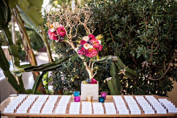 Centerpiece of gold branches and flowers on escort card table at wedding