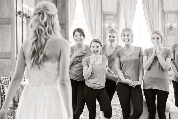 black and white photo of bridesmaids reacting to the bride's complete look