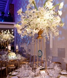 Wedding reception centerpiece of white flowers in a gold urn sitting on Art Decor risers