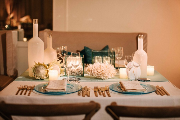 Ocean theme wedding with blue charger, coral centerpiece, protea, candles, gold flatware