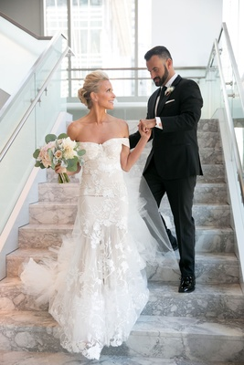 Bride brittany daniel actress in off shoulder form fitting wedding dress groom in suit and tie stair