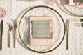 gold-rimmed transparent charger, gold flatware, blush napkin, grey menu, textured white linens
