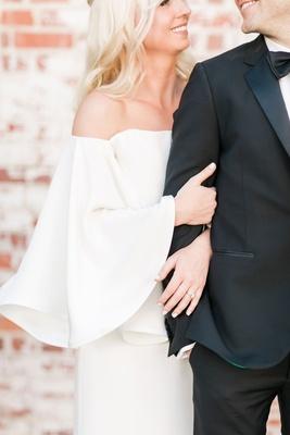 Bride wearing bell sleeves and groom in tuxedo