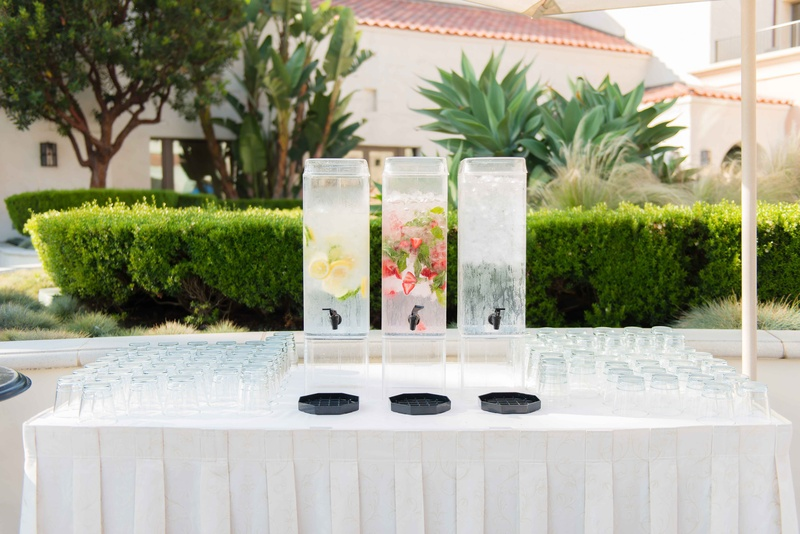Outdoor wedding drink table water dispensers lemon cucumber strawberry mint ice water