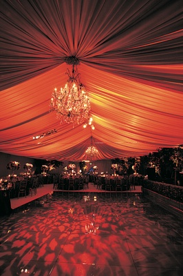 Wedding reception with amber draping, chandeliers, and black dance floor