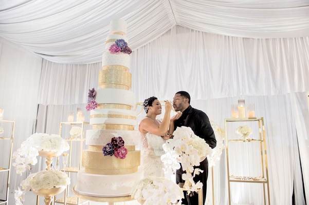 Bride feeding groom cake tall white and gold sparkle wedding cake with flowers on tiers white orchid