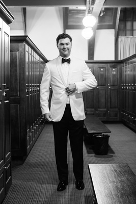 Black and white photo of groom in white tuxedo jacket and bow tie