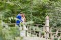 wedding portrait on bridge bride in hayley paige wedding dress groom in azure blue suit woods