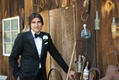 Groom in tuxedo next to cabin with horse shoes