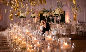 bride and groom alone in wedding reception space with classic white and gold colors