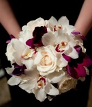 Bridesmaid holding white rose and purple orchid bouquet