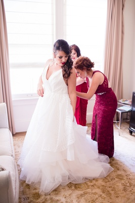 bridesmaids in wine hued dresses help bride into hayley paige wedding dress