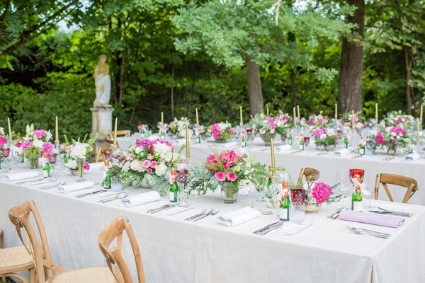 outdoor wedding reception in france white table wood vineyard chairs pink white flowers gold candles