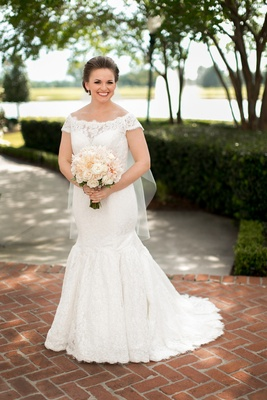 Bride in an off-the-shoulder, fit-and flare Sottero and Midgley lace dress, veil & light bouquet
